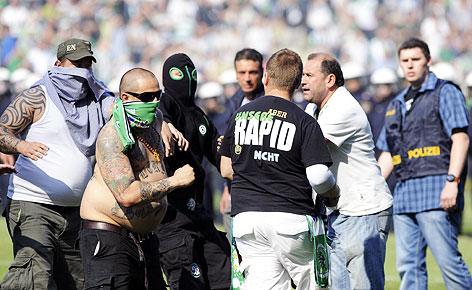 Maskierte Rapid Fans laufen während des Spieles auf das Spielfeld