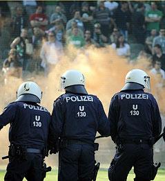 Polizisten, dahinter Rauch vom bengalischen Feuer