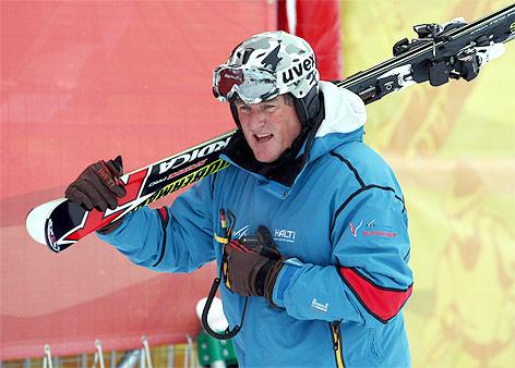 FIS-Renndirektor Günter Hujara trägt Skier auf der Schulter