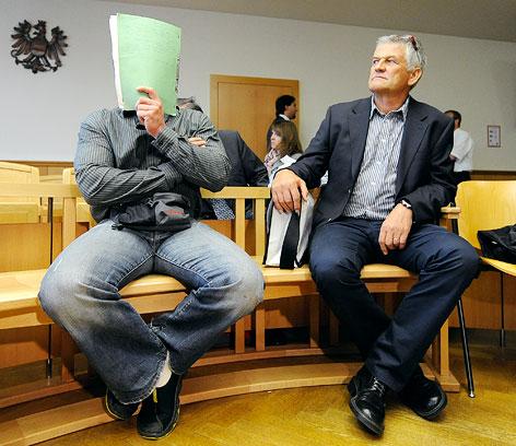 Der im Dopingprozess Mitangeklagte Karl Heinz R. mit Mappe vor dem Gesicht sitzt neben Ex-ÖSV-Betreuer Walter Mayer auf der Anklagebank