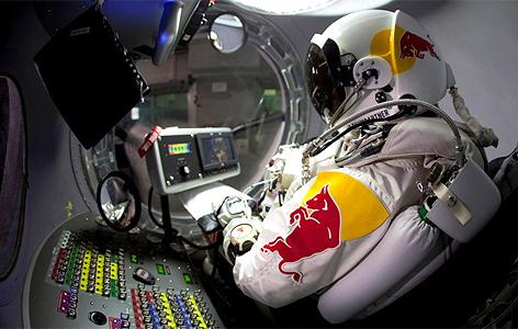 Felix Baumgartner mit Druckanzug sitzt in einer kleinen Kapsel mit Bedienelementen