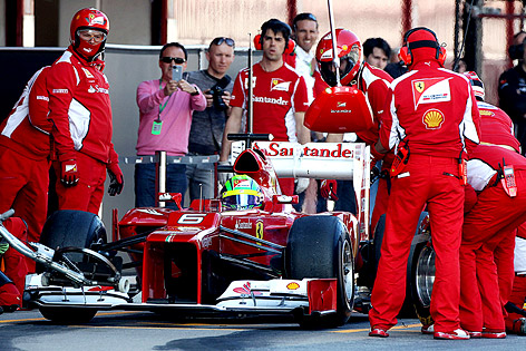 Mechaniker stehen neben Ferrrari von Felipe Massa in der Box