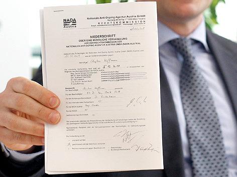 Der Vorsitzende der Rechtskommission der Nationalen Anti-Doping-Agentur (NADA), Gernot Schaar hält eine Niederschrift über eine mündlicher Verhandlung vor der Rechtskommission der NADA hoch