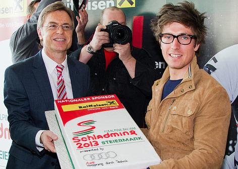 Marcel Hirscher und Raiffeisen-Marketing-Chef Leodegar Pruschak halten eine Schladming-Torte