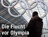 Mann geht in einem Londoner Bahnhof bei den Olympischen Ringen vorbei