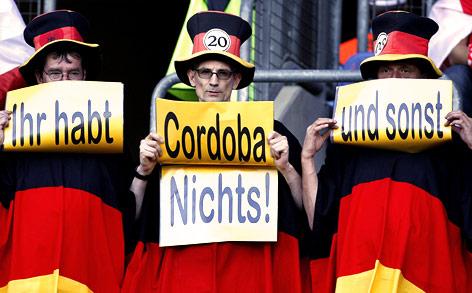 """Drei Deutschlandfans halten vier Zetteln mit den Aufschriften """"Ihr habt"""", """"Cordoba"""", """"und sonst"""" und """"nichts"""""""