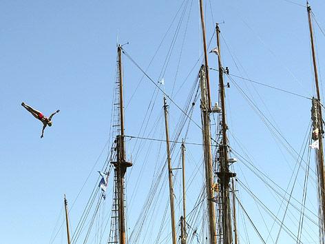 Turmspringer vor einem Segelschiff