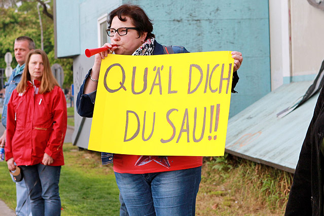 """Eine Zuschauerin hält ein Schild mit der Aufschrift """"Quäl dich du Sau!"""""""