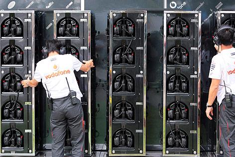 Formel-1-Crewmitglieder vor einer Wand mit Kopfhörern