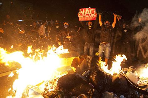 Demonstranten vor brennendem Müllhaufen