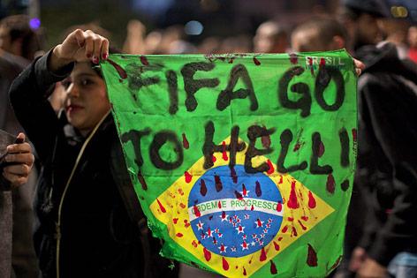 """Demonstrantin hält ein Plakat mit der Aufschrift """"FIFA GO TO HELL """""""