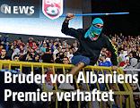 Ein vermummter Mann mit Stange überspringt eine Stadionabsperrung