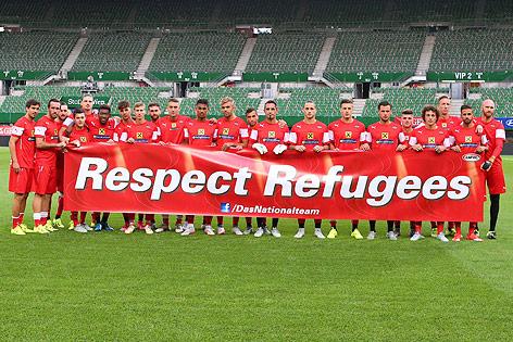 """Das ÖFB-Team hält ein Transparent mit der Aufschrift """"Respect Refugees"""""""