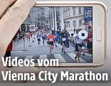 Person fotografiert mit einem Handy die Läufer