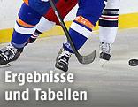 Füße von Eishockey-Spielern und Puck