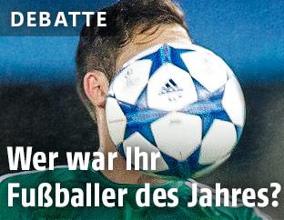 Von einem Ball verdecktes Gesicht eines Fußballers