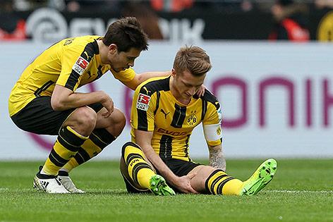 Dortmunds Marco Reus sitzt neben Mannschaftskollege Raphael Guerreiro verletzt am Boden