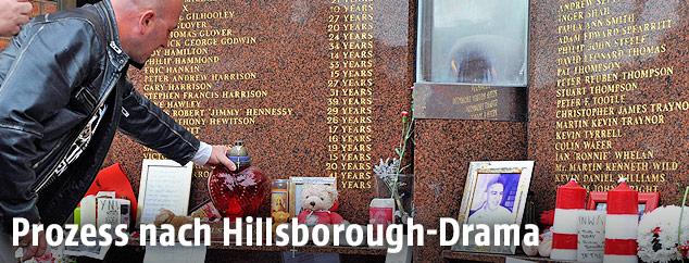 Ein Mann stellt eine Kerze an die Gedenkstätte vor dem Hillsborough-Stadion in Sheffield