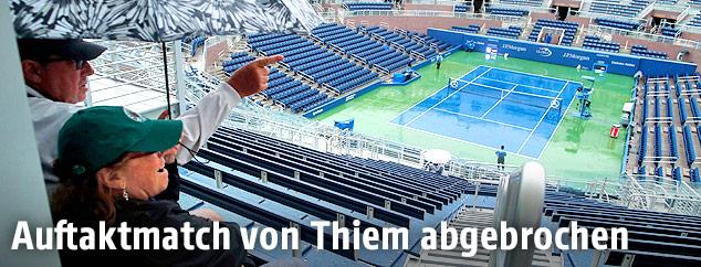 Zwei Tennisfans mit Regenschirm sitzen auf leeren Rängen und blicken auf den regennassen Tennisplatz