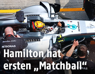Lewis Hamilton im Cockpit umgegen von Serviceleuten