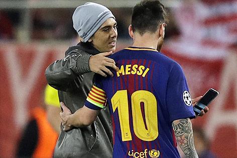 Fan mit Handy in der Hand umarmt Barca-Stürmer Lionel Messi auf dem Spielfeld