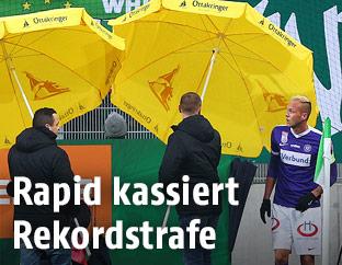 Ordner mit Sonnenschirmen und Raphael Holzhauser (A. Wien)