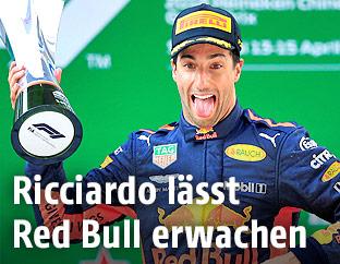 Red-Bull-Fahrer Daniel Ricciardo jubelnd mit herausgestreckter Zunge und Pokal