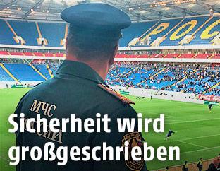 Russischer Polizist blickt in einem Stadion auf den Rasen