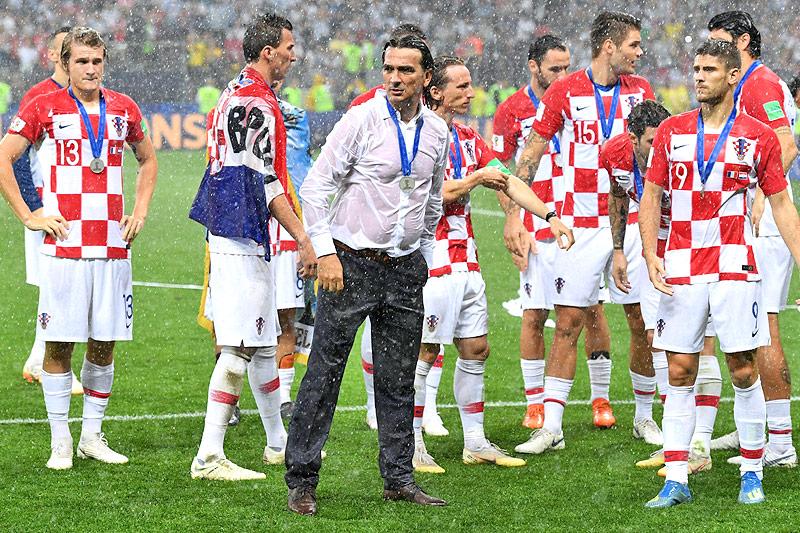 Der kroatische Teamchef Zlatko Dalic steht mit Spielern im Regen